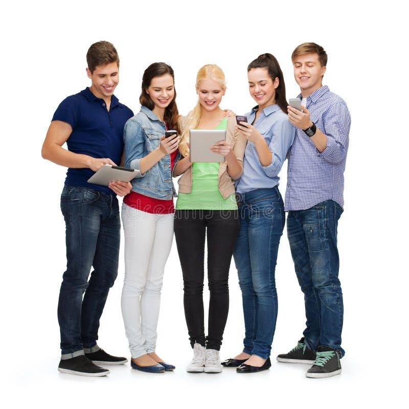 Усмехаясь студенты используя smartphones и ПК таблетки стоковое фото