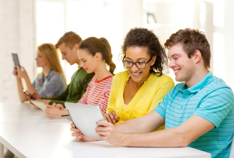 Усмехаясь студенты смотря ПК таблетки на школе стоковое изображение
