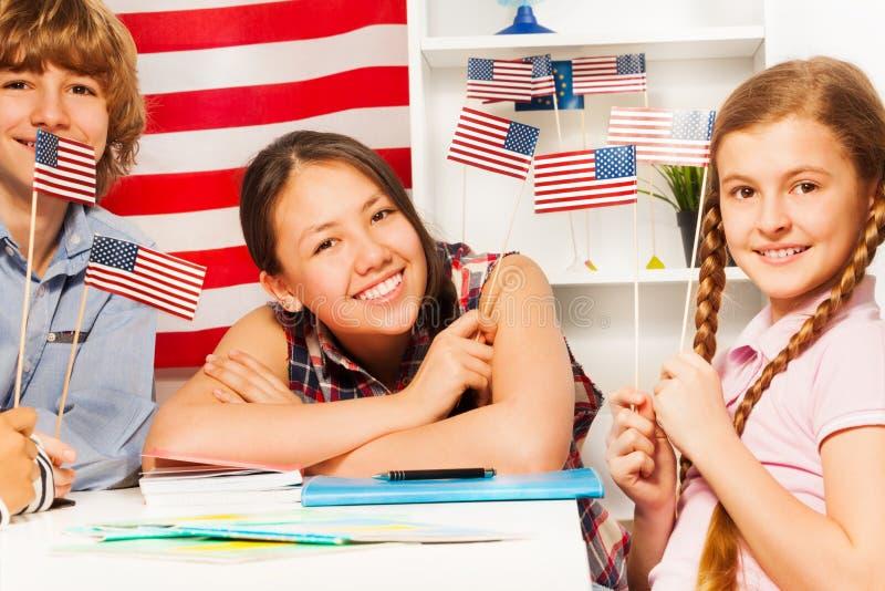 Усмехаясь студенты с американскими флагами на классе стоковое изображение