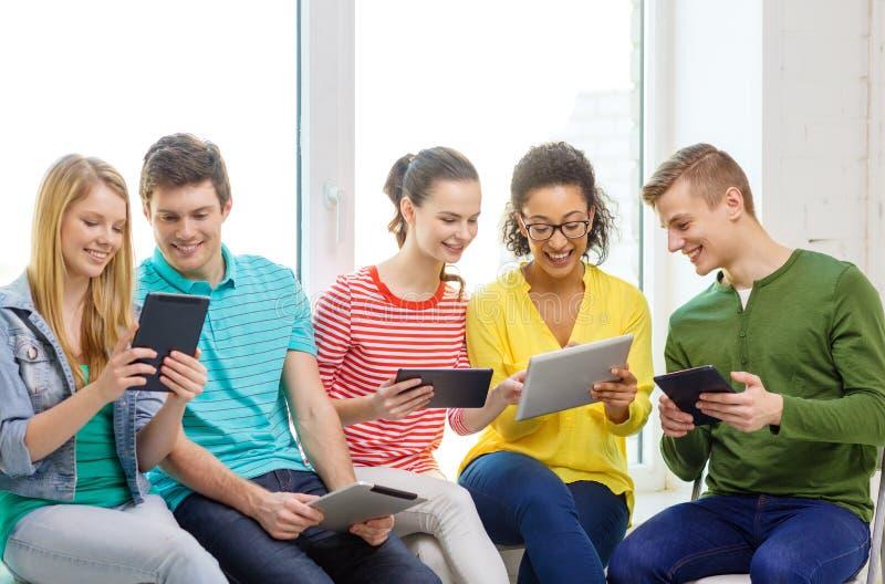 Усмехаясь студенты с компьютером ПК таблетки стоковые фото