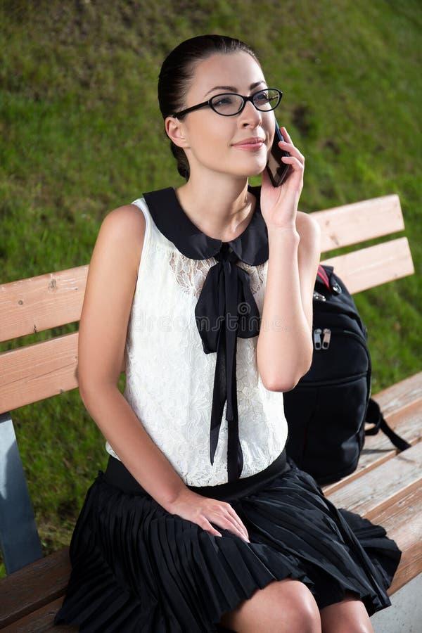Усмехаясь студент или девушка школы говоря на мобильном телефоне в парке стоковые изображения rf
