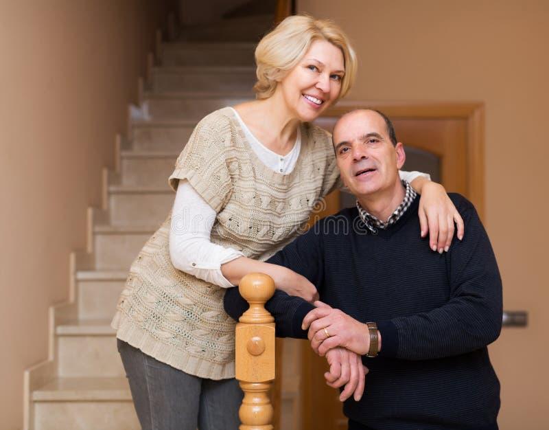 Усмехаясь супруги полагаясь против лестницы стоковое изображение