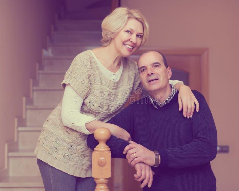 Усмехаясь супруги полагаясь против лестницы стоковые фото