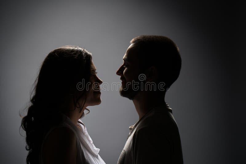 Усмехаясь супруги смотря один другого в темноте стоковое изображение rf
