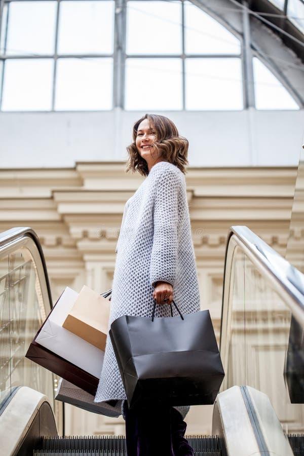 Усмехаясь счастливая женщина в связанном ярком пальто лета с хозяйственными сумками на эскалаторе в торговом центре города стоковые изображения rf