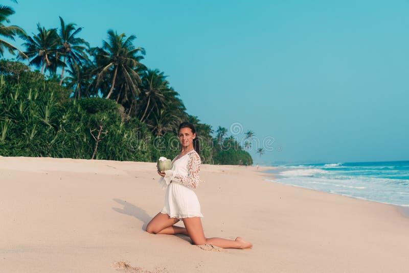 Усмехаясь счастливая маленькая девочка отдыхая на море, играя и имея потеху на пляже, нося стильные одежды, выпивая a стоковые фотографии rf