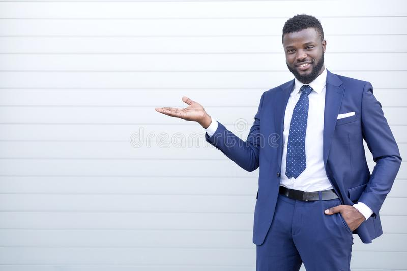 Усмехаясь счастливый африканский бизнесмен в костюме стоя против стены указывая на что-то стоковое изображение