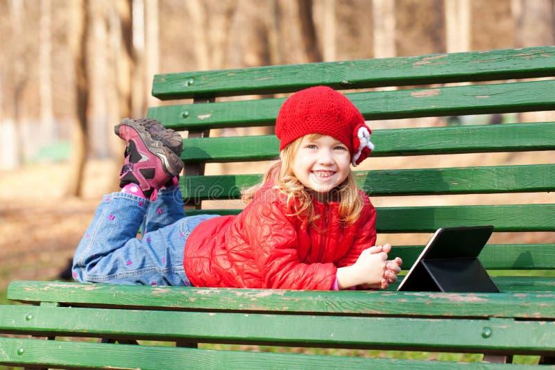 Усмехаясь счастливая маленькая девочка используя таблетку outdoors. стоковое изображение