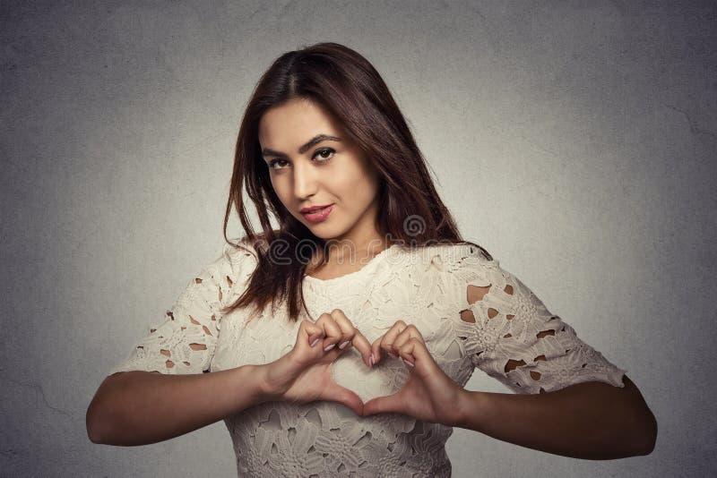 Усмехаясь счастливая молодая женщина делая сердце подписывает с руками стоковые фотографии rf