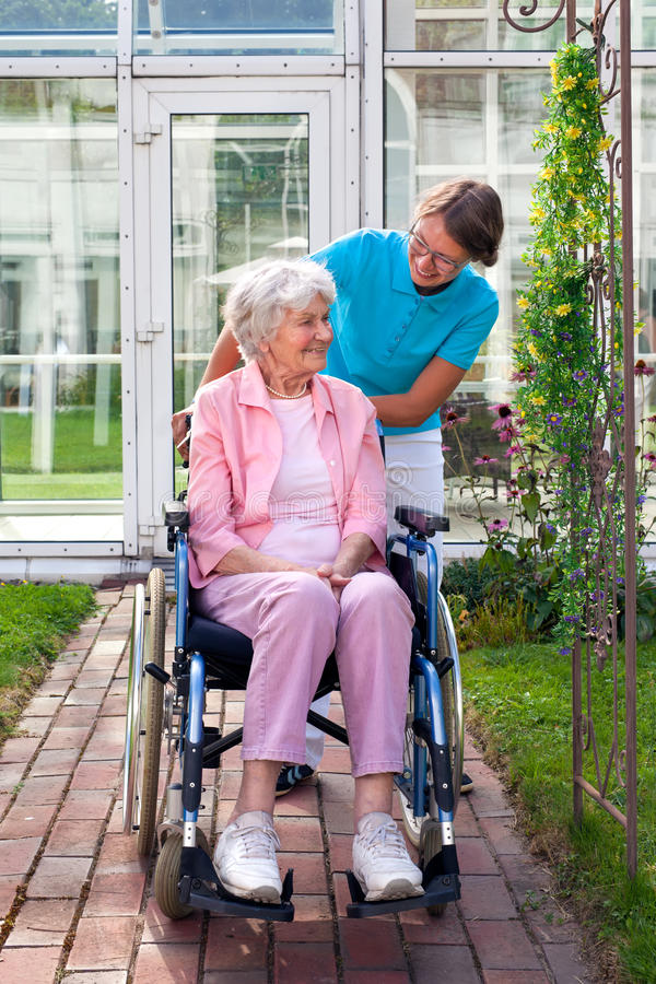 Усмехаясь счастливая старшая дама в кресло-коляске стоковые изображения rf