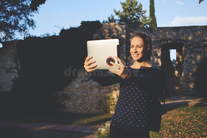 Усмехаясь счастливая студентка фотографирует с передней цифровой камерой таблетки стоковые изображения rf