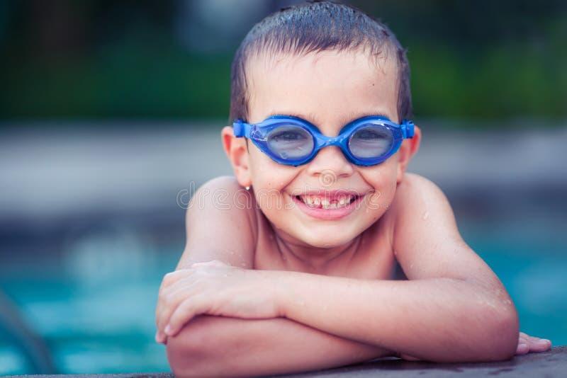 Усмехаясь счастливый мальчик в бассейне стоковое фото