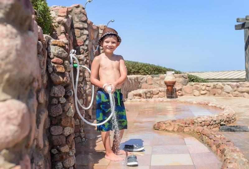 Усмехаясь счастливый молодой мальчик полоща с шлангом стоковые фотографии rf
