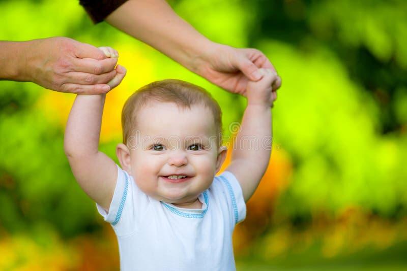 Усмехаясь счастливый младенец уча идти стоковое фото rf