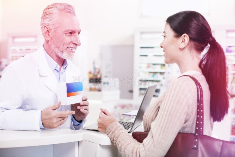 Усмехаясь таблетки druggist показывая к заинтересованной женщине в аптеке стоковые фотографии rf