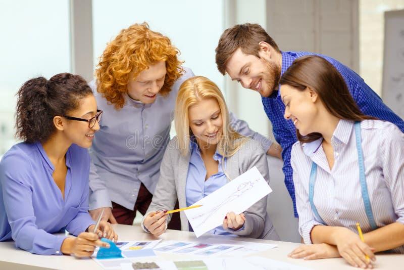 Усмехаясь творческая команда смотря эскиз стоковое фото rf