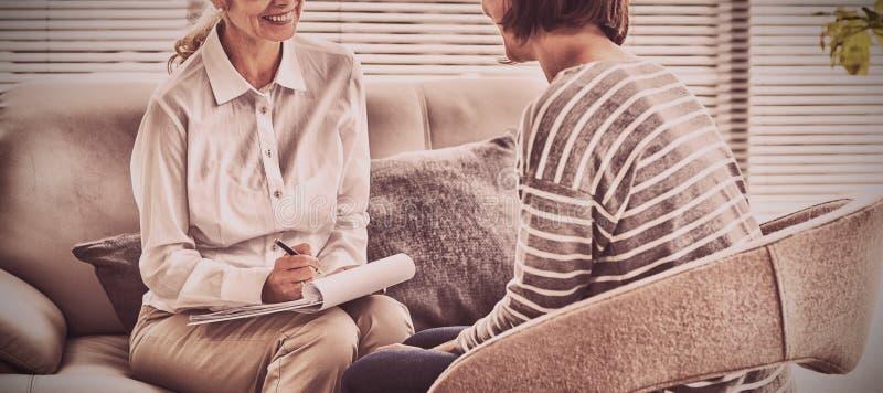 Усмехаясь терапевт с пациентом стоковое изображение