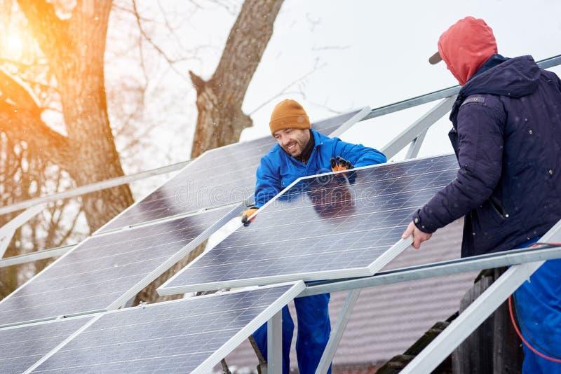 Усмехаясь техники устанавливая голубые солнечные модули на крыше современного дома как устойчивый источник альтернативной энергии стоковое фото