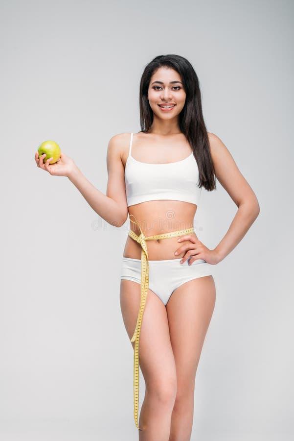 усмехаясь тонкая Афро-американская женщина с измеряя лентой на яблоке удерживания талии стоковые фотографии rf