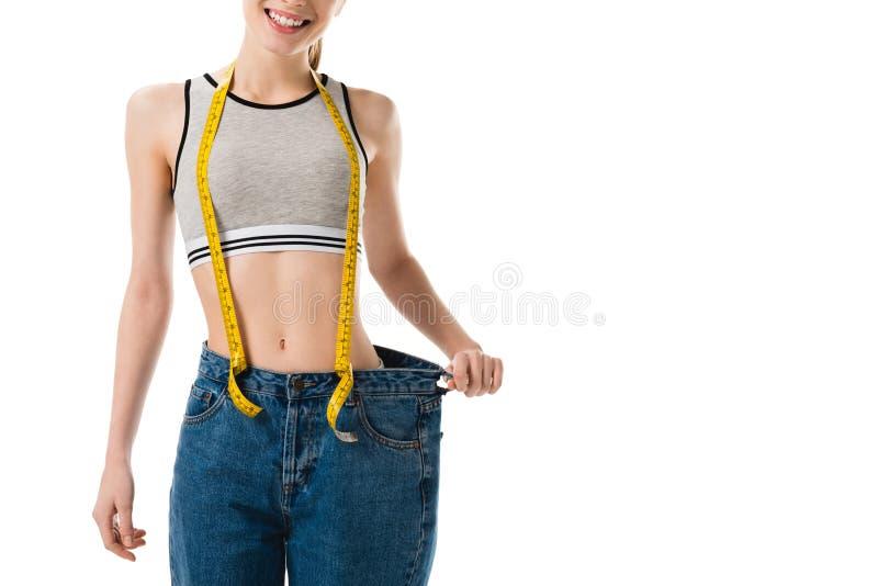 усмехаясь тонкая женщина с измеряя лентой в слишком больших джинсах стоковое изображение