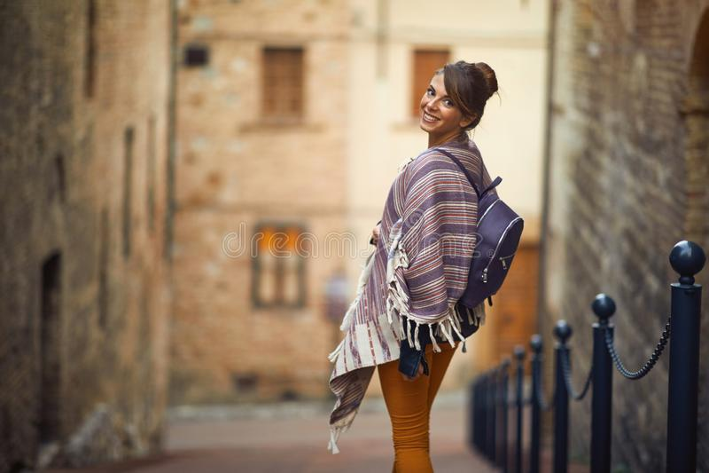Усмехаясь туристская женщина путешествуя и смотря архитектура на каникулах стоковое изображение