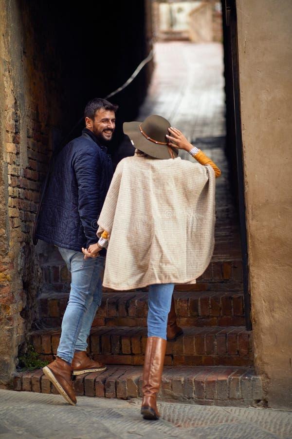 Усмехаясь туристские пары путешествуя и смотря архитектура на каникулах стоковые изображения