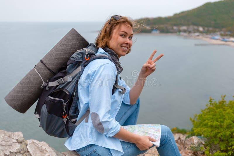 Усмехаясь турист женщины сидя на скалистом уступе с картой в его руках и представляя для камеры r стоковые изображения