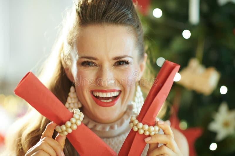 Усмехаясь ультрамодное удерживание домохозяйки служа красные салфетки обедающего стоковые фото