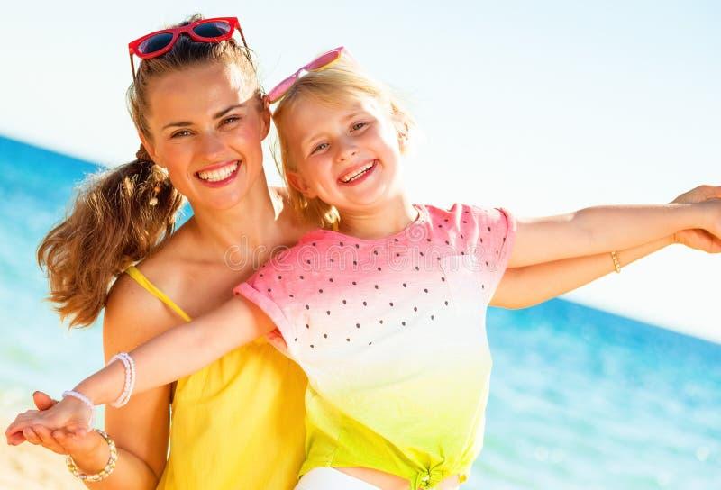 Усмехаясь ультрамодные мать и дочь на seashore имея время потехи стоковые фотографии rf