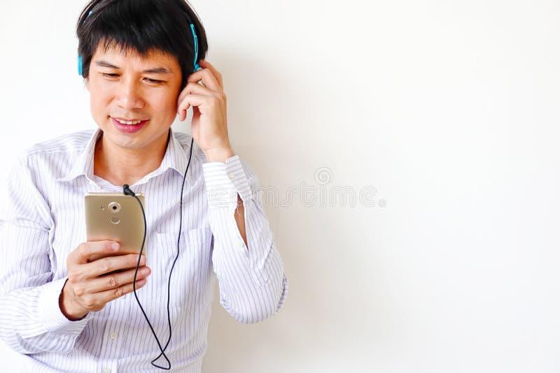Усмехаясь усаживание человека ослабленное на поле слушая музыку на на стоковое изображение rf