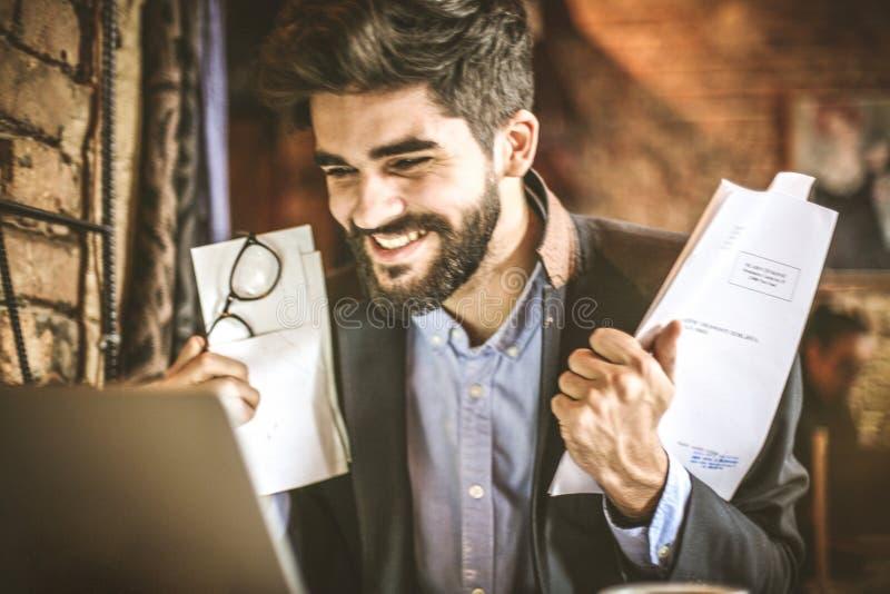 Усмехаясь успешный бизнесмен с документом стоковая фотография