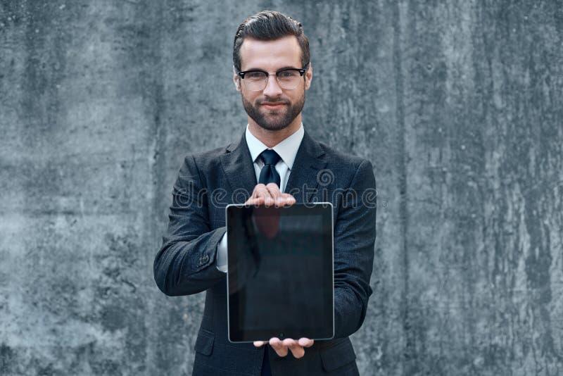 Усмехаясь успешный молодой бизнесмен на конкретной предпосылке внутри стоковое фото
