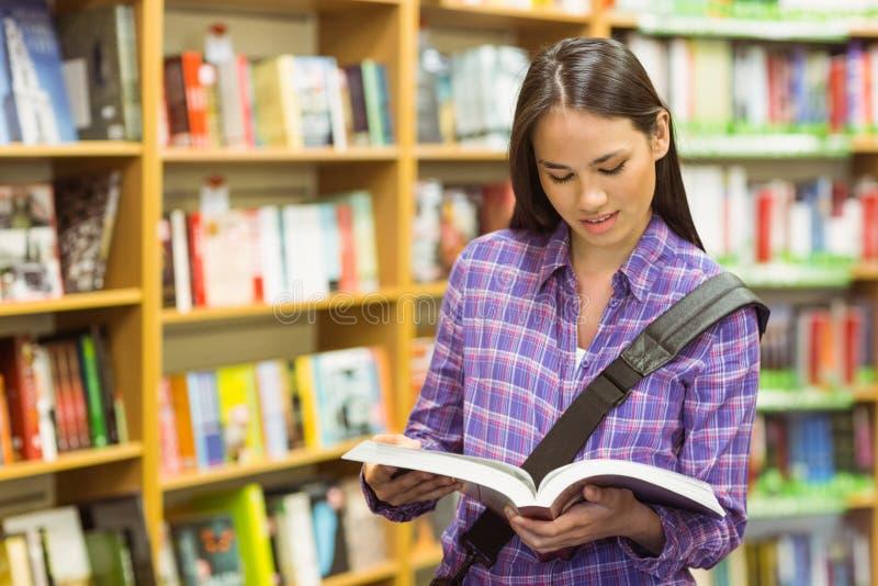 Усмехаясь учебник чтения студента университета стоковая фотография rf