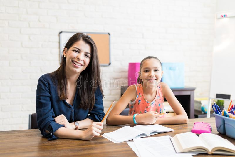 Усмехаясь учитель давая частные уроки девушки после школы стоковая фотография rf