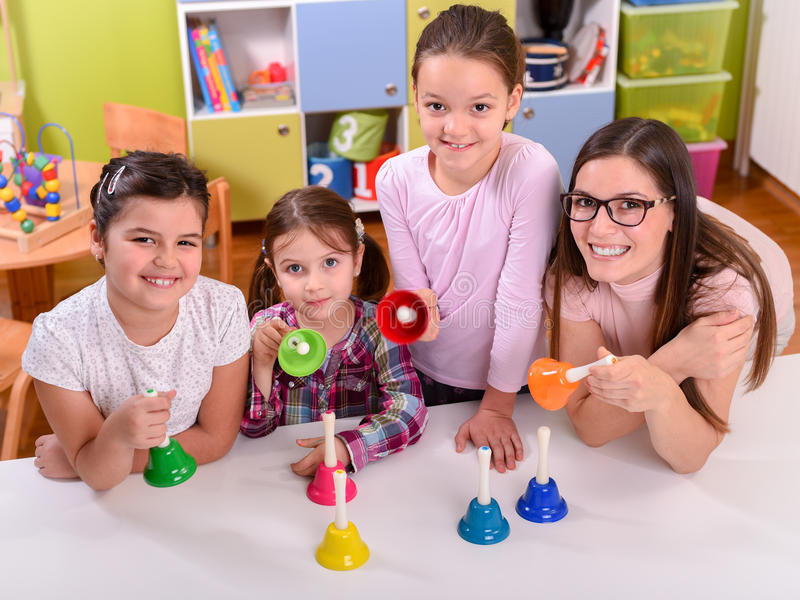 Усмехаясь учитель при милые дети держа руку колоколы музыки стоковая фотография
