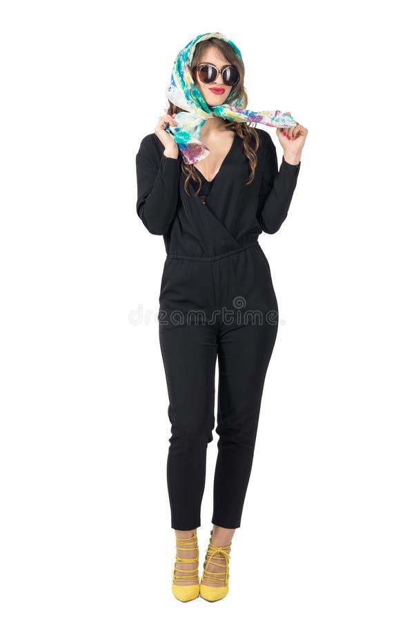 Усмехаясь ультрамодная красота в солнечных очках комбинезона нося связывая головной платок стоковые фото