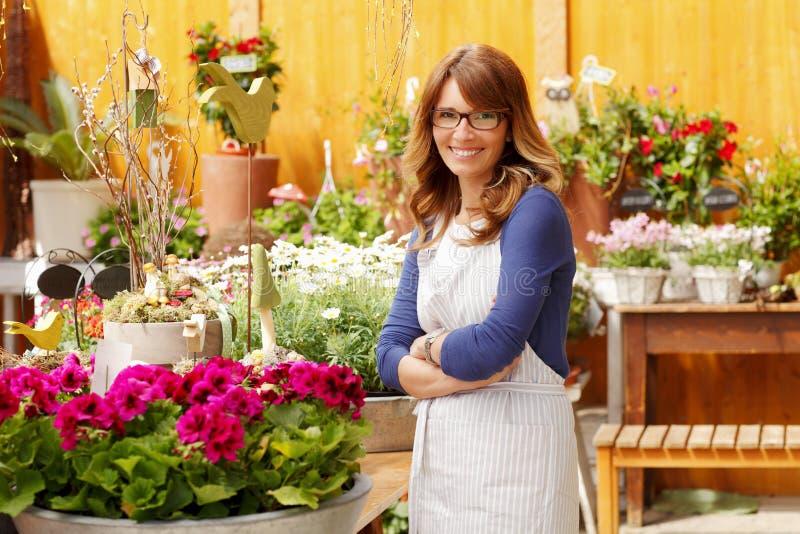 Усмехаясь флорист женщины, предприниматель цветочного магазина мелкого бизнеса стоковые фото