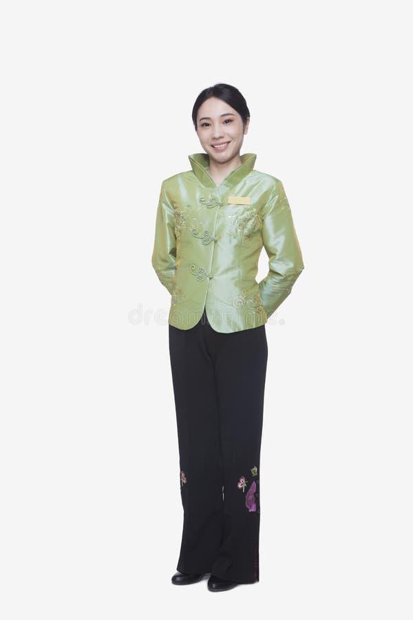 Усмехаясь хозяюшка ресторана/гостиницы в одежде традиционного китайския, во всю длину стоковые фото