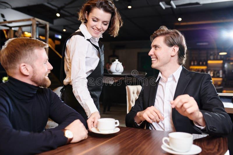 Усмехаясь чай официантки служа к бизнесменам стоковое фото rf