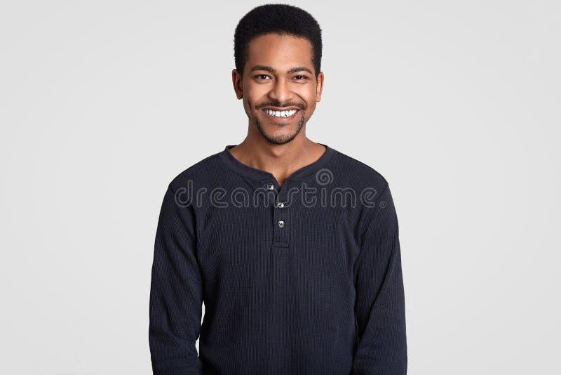 Усмехаясь человек Афро американский имеет зубастую улыбку, показывает белые зубы, был в высоком духе, радуется приятные моменты в стоковые фотографии rf