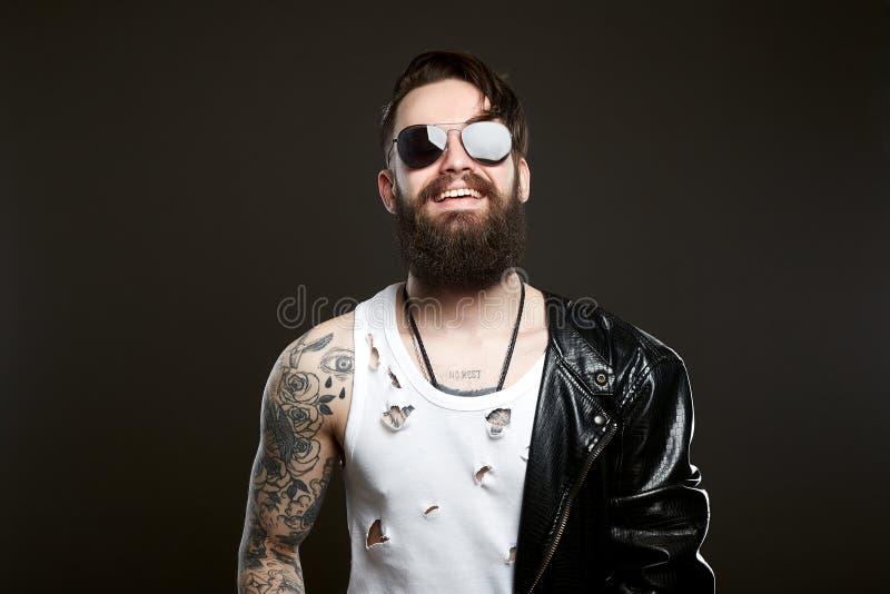 Усмехаясь человек бородатый сексуальный мальчик в кожаном пальто стоковые изображения rf