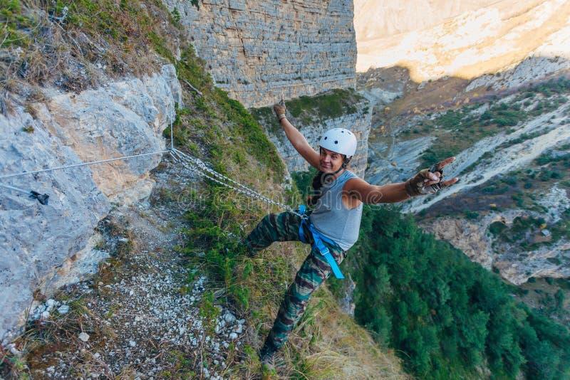 Усмехаясь человек вися на скале на веревочках стоковые фотографии rf