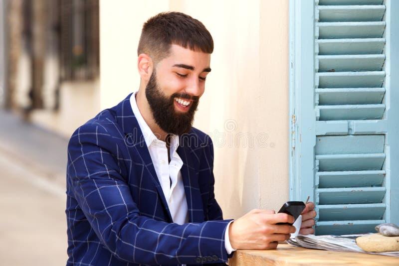 Усмехаясь человек в деловом костюме сидя с мобильным телефоном стоковое фото rf