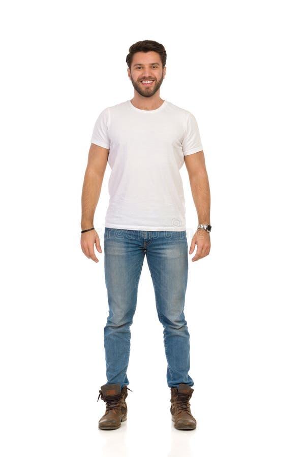 Усмехаясь человек в джинсах и белой футболке стоящ и смотрящ камера r стоковые фотографии rf