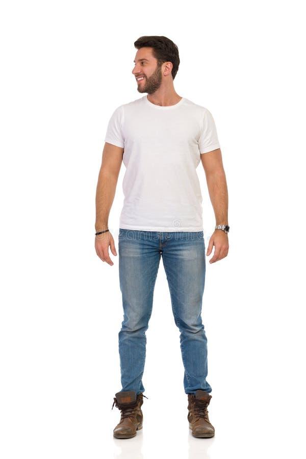 Усмехаясь человек в джинсах и белой футболке стоящ и смотрящ прочь Вид спереди стоковое изображение