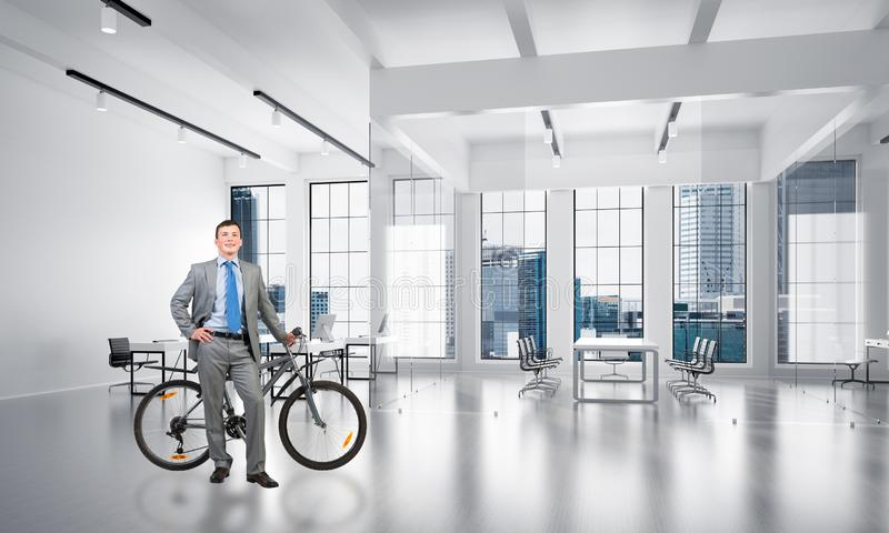 Усмехаясь человек в положении делового костюма с велосипедом стоковые изображения