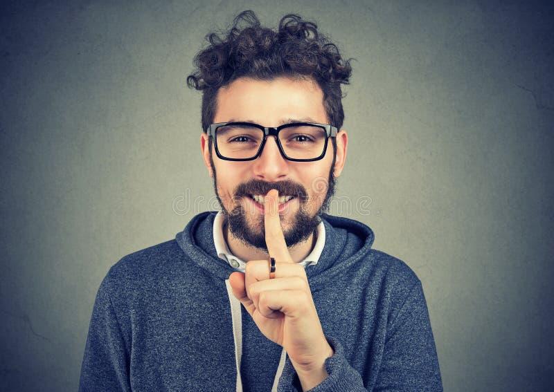Усмехаясь человек держа палец на губах стоковое изображение