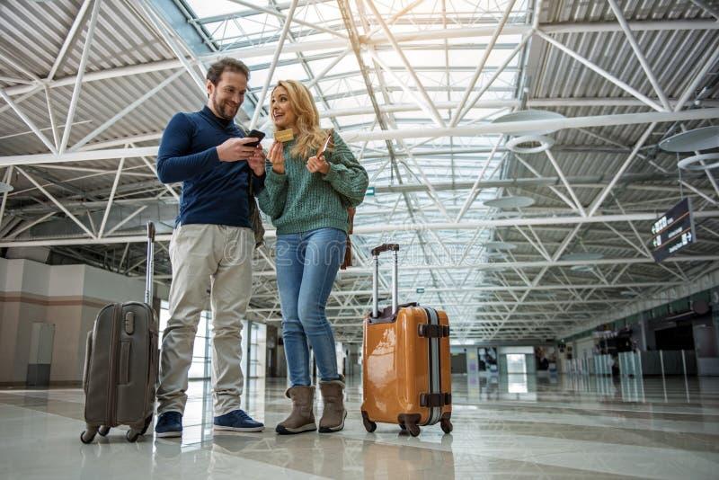 Усмехаясь человек и женщина оплачивая для посадочного талона стоковое изображение rf