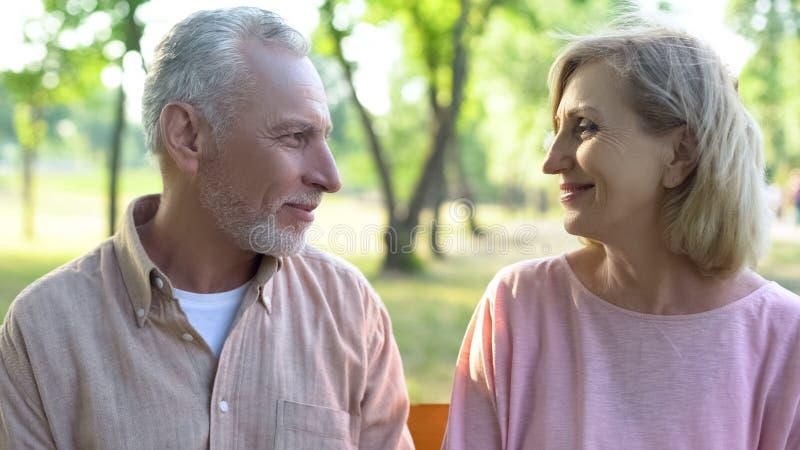 Усмехаясь человек и женщина смотря один другого, романтичные отношения, счастье даты стоковое фото