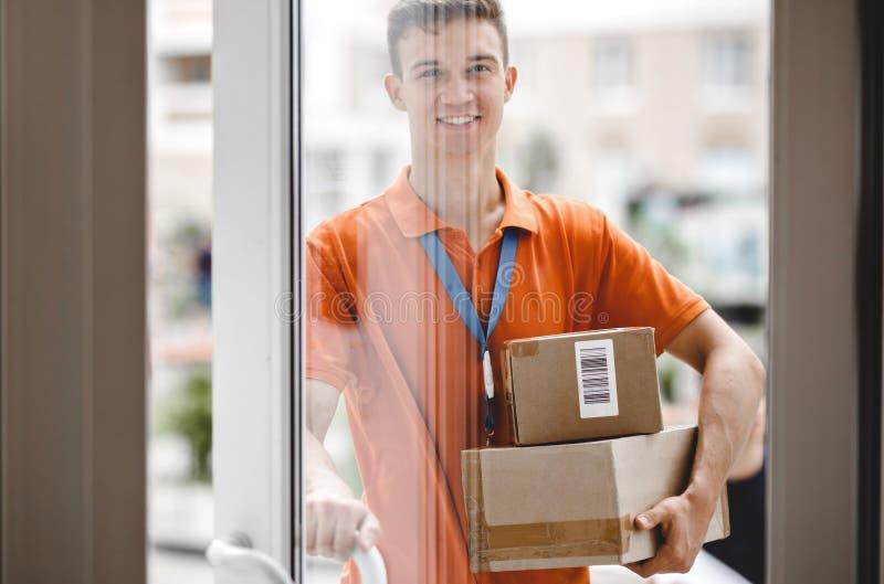 Усмехаясь человек нося оранжевую футболку и бирку имени стоит за стеклянной дверью и держит ручку двери стоковые изображения rf